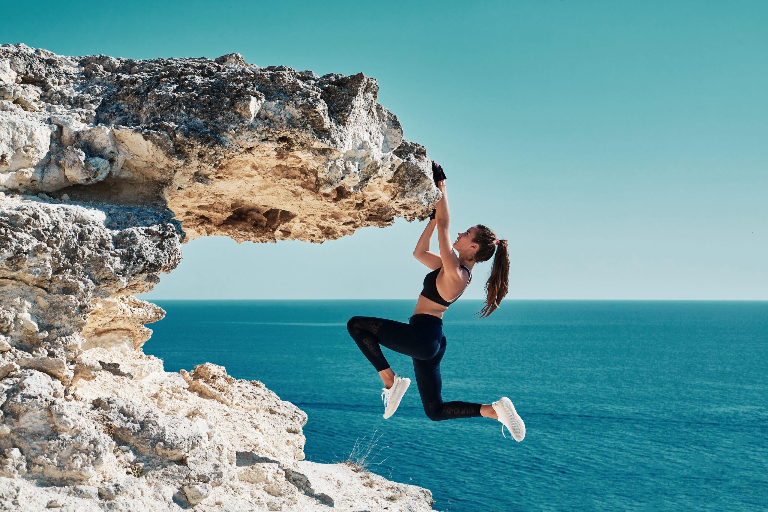 Vrouw die aan rots hangt in sportkledij