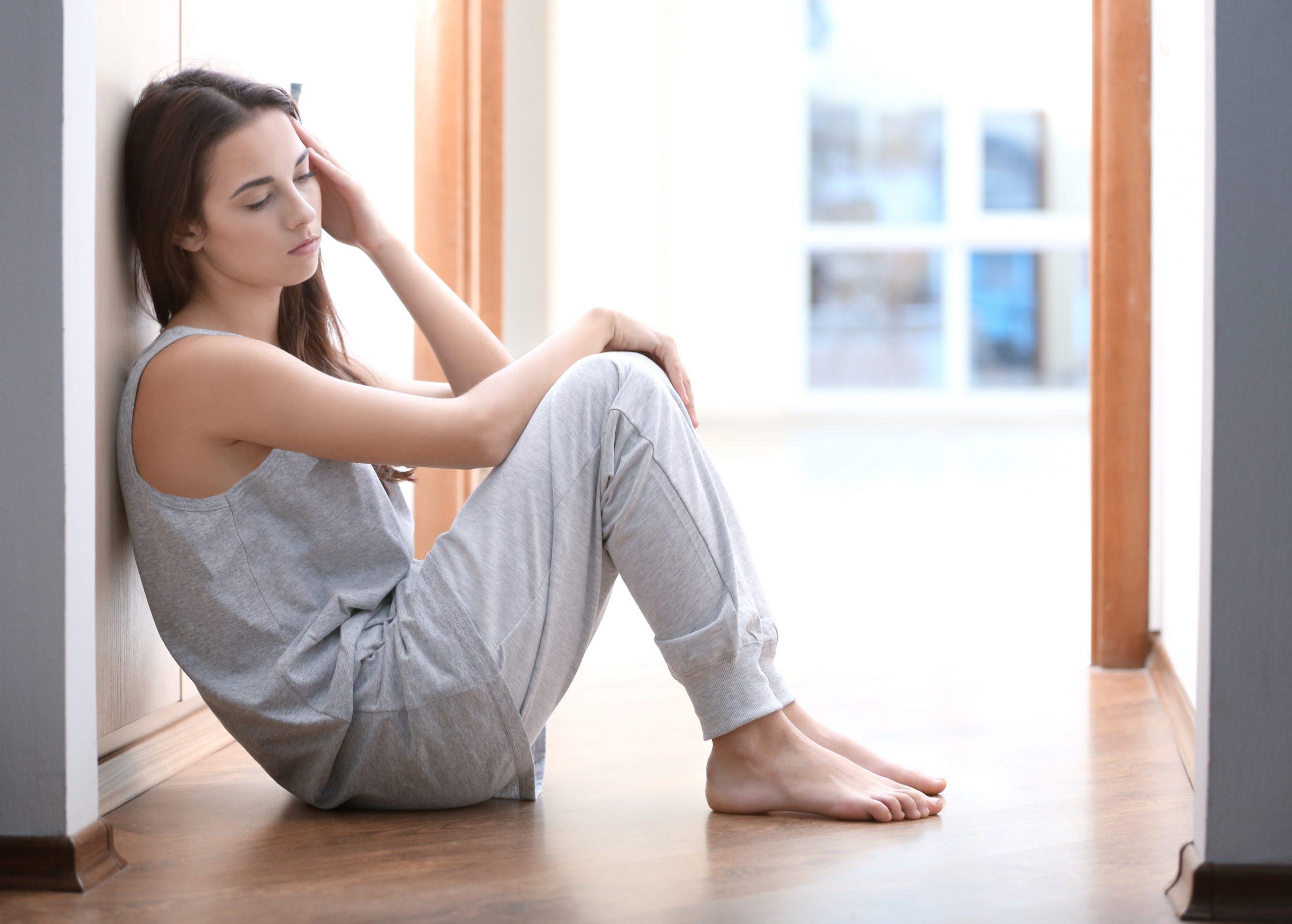 Vrouw die klachten heeft en op de grond zit