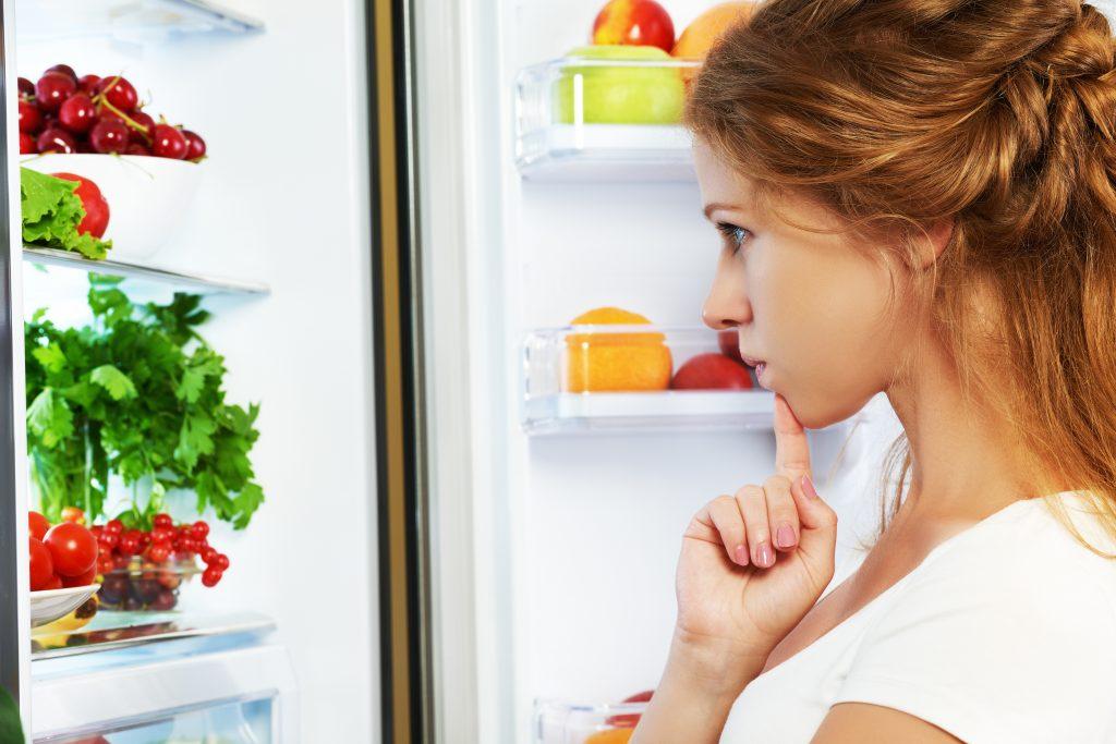 vrouw kijkt naar inhoud frigo